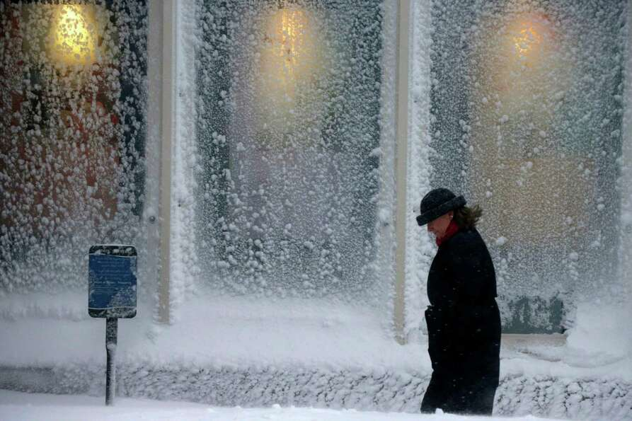 A woman walks past windows covered with snow at the Seaport World Trade Center in Boston early Satur