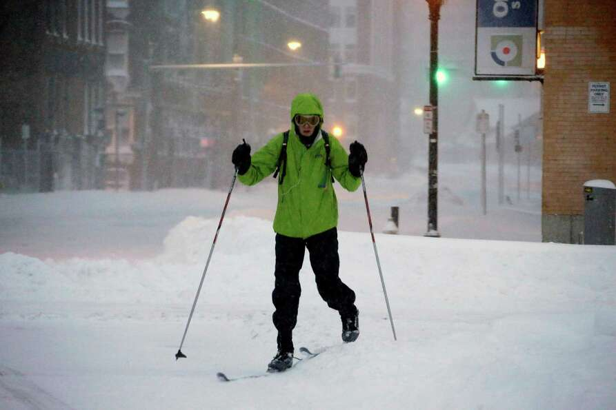 A pedestrian uses skis to travel through the deserted snow-covered streets of Boston early Saturday,