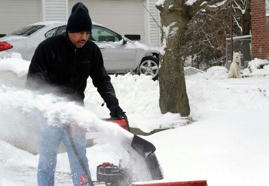 Stan Hansen clears his driveway of overnight snow on Saturday Feb. 9, 2013 in Delmar, N.Y. .(Michael