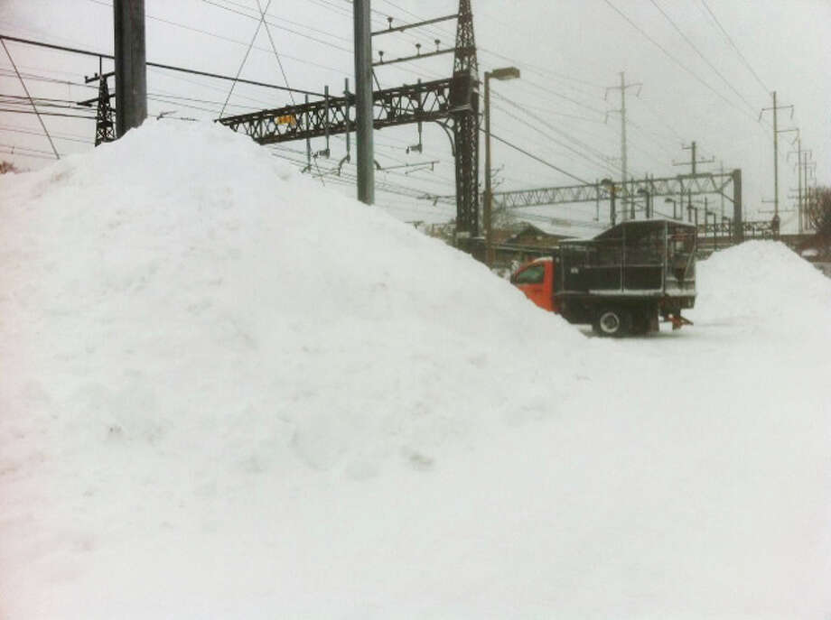 Towering mounds of snow plowed in the Fairfield Railroad Station's parking lots early Saturday dwarf one of the town trucks on the scene.  FAIRFIELD CITIZEN, CT 2/9/13 Photo: John Schwing / Fairfield Citizen contributed