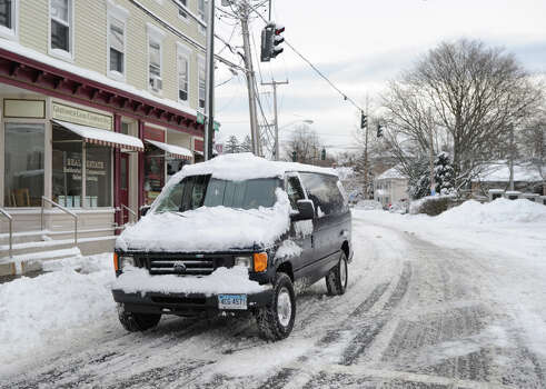 A vehicle covered with snow heads through downtown Byram during the aftermath of the blizzard that hit Greenwich, Conn., Saturday morning, Feb. 9, 2013. Photo: Bob Luckey / Greenwich Time