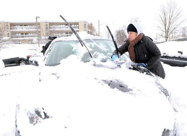 Milagros Castillo clears snow off her car during the aftermath of the blizzard at the Armstrong Court Public Housing Complex, Greenwich, Conn., Saturday morning, Feb. 9, 2013. Castillo said that she had to get into New York City to visit her mother who is in the hospital. Photo: Bob Luckey / Greenwich Time