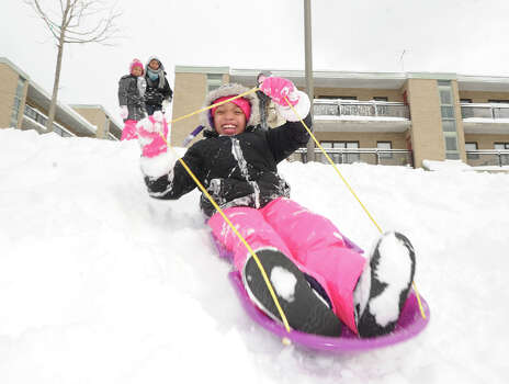 Paige Pray, 8, enjoys riding her sled in the snow at the Armstrong Court Public Housing Complex during the aftermath of the blizzard that hit Greenwich, Conn., Saturday morning, Feb. 9, 2013. Photo: Bob Luckey / Greenwich Time