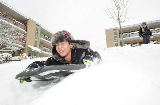 Daniel Estrella, 9, enjoys a sled ride during the aftermath of the blizzard at the Armstrong Court Public Housing Complex, Greenwich, Conn., Saturday morning, Feb. 9, 2013. Photo: Bob Luckey / Greenwich Time