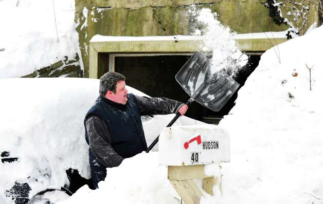 Joe Hudson digs his car out of the snow in Danbury Saturday, Feb. 9, 2013. Photo: Michael Duffy / The News-Times