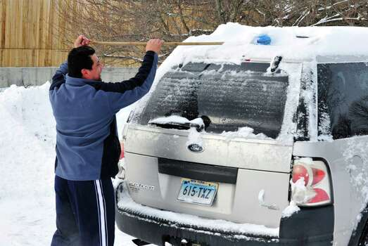 Antonio Vtrera clears snow off his car roof in Danbury Saturday, Feb. 9, 2013. Photo: Michael Duffy / The News-Times