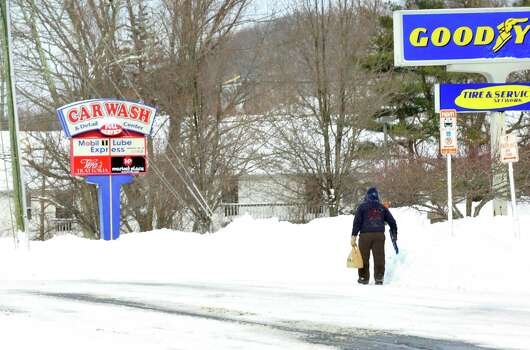 A lone pedestrian with a snow shovel walks along Mill Plain in Danbury Saturday, Feb. 9, 2013. Photo: Michael Duffy / The News-Times