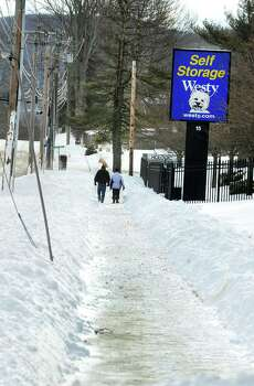 A couple walk in the snow along Kenosia Avenue in Danbury Saturday, Feb. 9, 2013. Photo: Michael Duffy / The News-Times