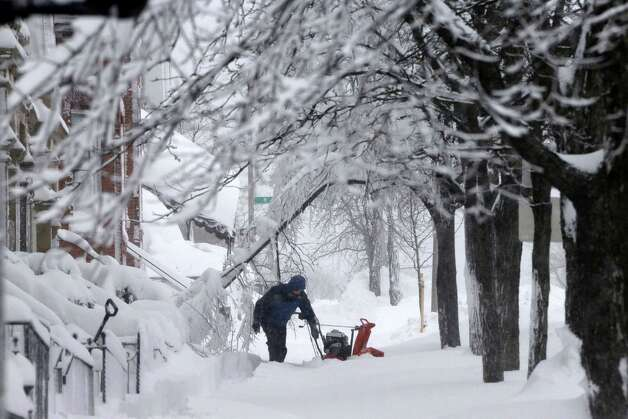 A man clears snow from the front of his home on Third Street in the South Boston neighborhood of Boston on Saturday, Feb. 9, 2013. Photo: Gene J. Puskar