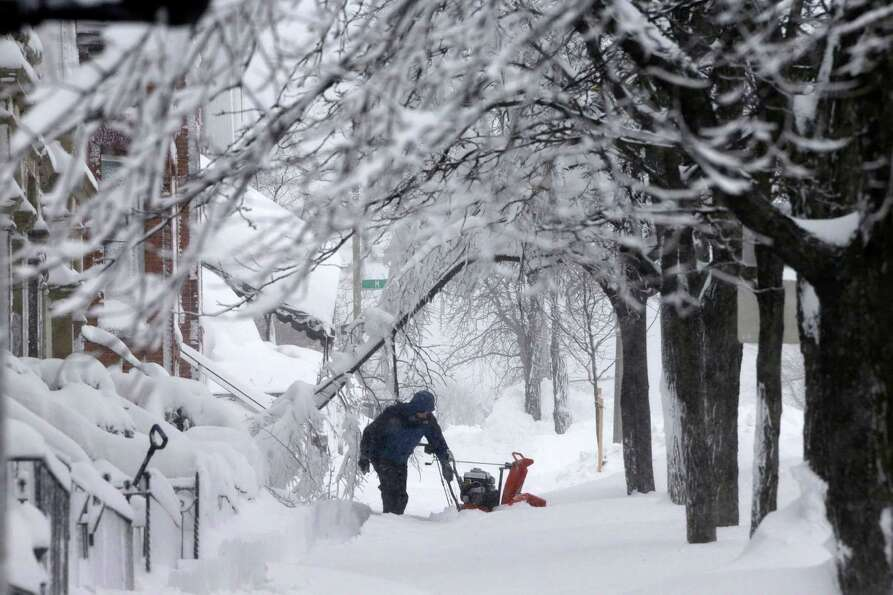 A man clears snow from the front of his home on Third Street in the South Boston neighborhood of Bos