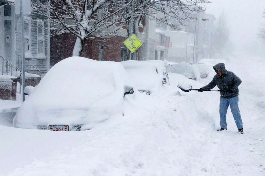 A man shovels out a car on Third street in the South Boston neighborhood of Boston, Saturday, Feb. 9, 2013. A behemoth storm packing hurricane-force wind gusts and blizzard conditions swept through the Northeast on Saturday, dumping more than 2 feet of snow on New England and knocking out power to 650,000 homes and businesses. Photo: Gene J. Puskar