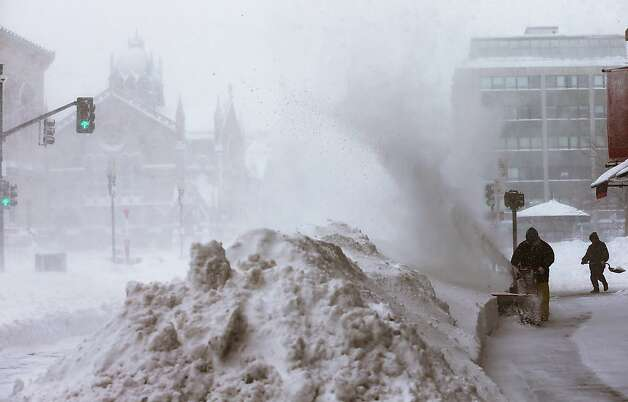 Workers clear snow from a sidewalk in the Back Bay neighborhood during a lingering blizzard on February 9, 2013 in Boston, Massachusetts. The powerful storm has knocked out power to 650,000 and dumped more than two feet of snow in parts of New England. Photo: Mario Tama, Getty Images