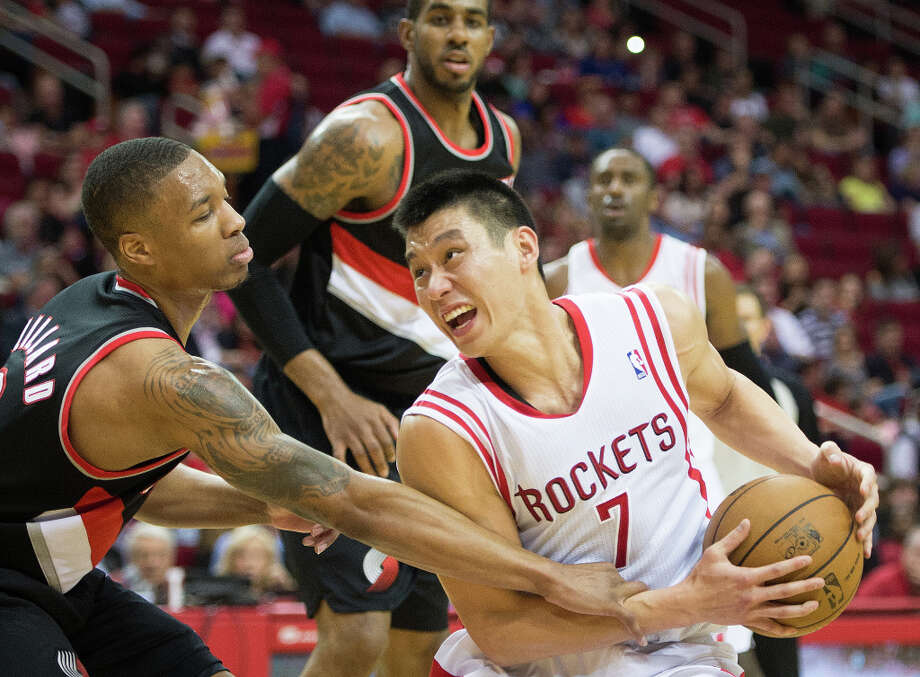 Rockets point guard Jeremy Lin is fouled by Portland point guard Damian Lillard. Photo: Smiley N. Pool, Houston Chronicle / © 2013  Houston Chronicle