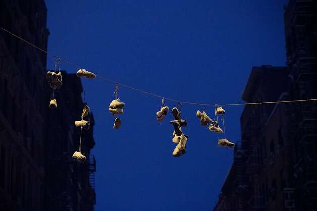 Snow gathers on shoes hung from power lines in the Lower East Side following a major winter storm on February 9, 2013 in New York City. New York City and much of the Northeast received a foot or more of snow through Saturday morning with possible record-setting blizzard conditions expected. Heavy snow warnings are in effect from New Jersey through southern Maine.  Photo: Andrew Kelly, Getty Images