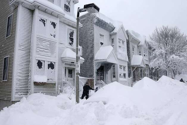 A man shovels the front of his home on Third street in the South Boston neighborhood of Boston, Saturday Feb. 9, 2013. A behemoth storm packing hurricane-force wind gusts and blizzard conditions swept through the Northeast on Saturday, dumping more than 2 feet of snow on New England and knocking out power to 650,000 homes and businesses. Photo: Gene J. Puskar, Associated Press