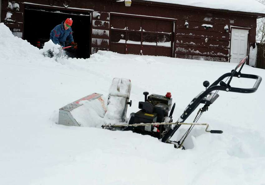 Joe Janeczko helps dig his neighbor out of the snow in East Windsor, Conn. on Saturday, Feb. 9, 2013