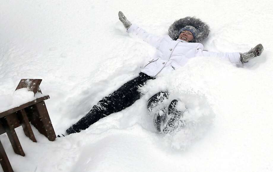 Nicole Lacoursière of North Andover, Mass. makes a snow angel Saturday, Feb. 9, 2013 in some 24 inches of snow which fell in her yard. A behemoth storm packing hurricane-force wind gusts and blizzard conditions swept through the Northeast, dumping more than 2 feet of snow on New England and knocking out power to 650,000 homes and businesses. Photo: Elise Amendola, Associated Press