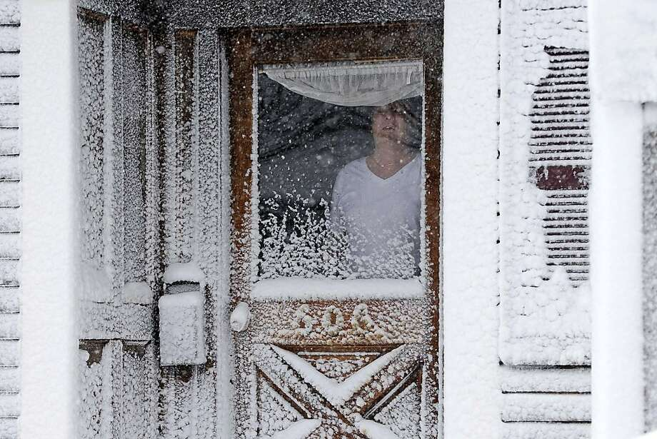 A resident of Third Street in the South Boston neighborhood of Boston looks out of his snow-coated front door Saturday, Feb. 9, 2013. A behemoth storm packing hurricane-force wind gusts and blizzard conditions swept through the Northeast overnight. Photo: Gene J. Puskar, Associated Press