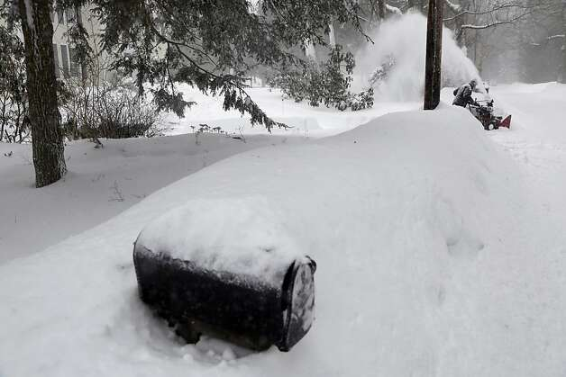Richard Langlois uses a snowblower to clear his driveway in North Andover, Mass. Saturday, Feb. 9, 2013. A behemoth storm packing hurricane-force wind gusts and blizzard conditions swept through the Northeast on Saturday, dumping more than 2 feet of snow on New England and knocking out power to 650,000 homes and businesses.  Photo: Elise Amendola, Associated Press