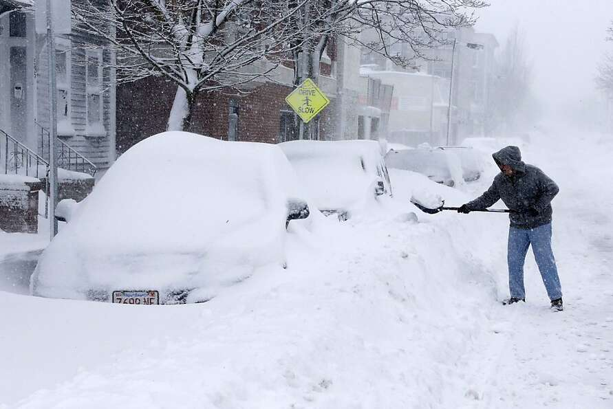 A man shovels out a car on Third street in the South Boston neighborhood of Boston, Saturday, Feb. 9