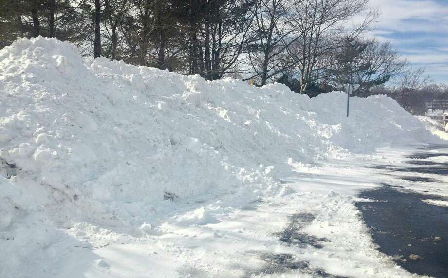 Mountainous piles of snow accumulated in the lot of the Westport Public Library on Saturday after snow-clearing operations.  WESTPORT NEWS, CT 2/9/13 Photo: Paul Schott / Westport News