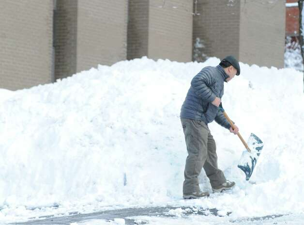 A man who said his name was Paul, clears snow from in front of a West Putnam Avenue business during the aftermath of the blizzard that hit Greenwich, Conn., Saturday morning, Feb. 9, 2013. Photo: Bob Luckey / Greenwich Time