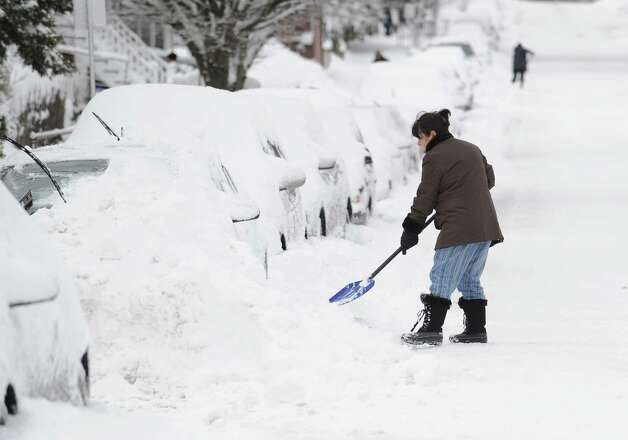 Tina Khoshaboo clears snow from her car on South Water Street in Byram during the aftermath of the blizzard that hit Greenwich, Conn., Saturday morning, Feb. 9, 2013. Photo: Bob Luckey / Greenwich Time