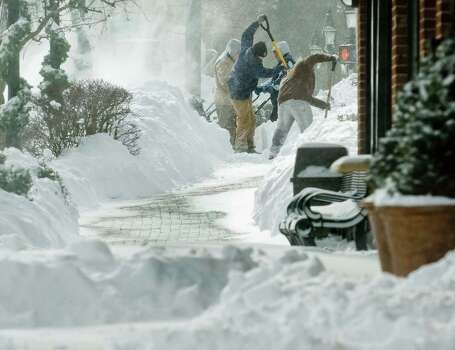 Workers shovel a sidewalk frantically in blowing snow on Main Street in Ridgefield after the snowstorm. Saturday, Feb. 9, 2013 Photo: Scott Mullin