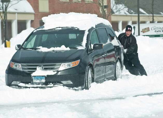 Rick Matte of Ridgefield tries to push his car after getting stuck in the Kohl's parking lot in Ridgefield. Saturday, Feb. 9, 2013 Photo: Scott Mullin / The News-Times Freelance