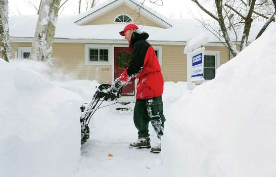 Ryan Adams uses a snowblower to clear the sidewalk in front of his home in Derby, Conn. Saturday, Feb. 9, 2013 following a severe blizzard that dumped up to three feet of snow across the state. Photo: Autumn Driscoll