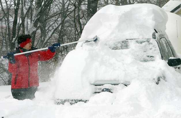Clare Howard-Pike works to clear her car after an overnight snowstorm, Saturday, Feb. 9, 2013 in Concord, N.H. A howling storm across the Northeast left the New York-to-Boston corridor shrouded in 1 to 3 feet of snow Saturday, stranding motorists on highways overnight and piling up drifts so high that some homeowners couldn't get their doors open. More than 650,000 homes and businesses were left without electricity. Photo: Jim Cole, Associated Press
