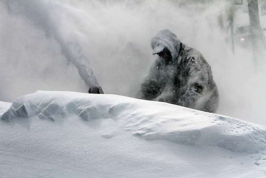 Neil Hodges uses a snow blower to clear drifting snow from in front of his home in Concord, N.H. on