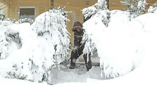 Frank Perry shovels snow from his front porch as the weight of the snow causes the bushes to sag, Saturday, Feb. 9, 2013, in Providence, R.I. A howling storm across the Northeast left the New York-to-Boston corridor shrouded in 1 to 3 feet of snow Saturday, stranding motorists on highways overnight and piling up drifts so high that some homeowners couldn't get their doors open. More than 650,000 homes and businesses were left without electricity. Photo: Stew Milne, Associated Press