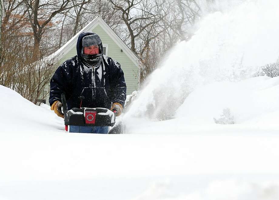 Moises Diaz uses a snowblower to clear his driveway in Derby, Conn. as residents face massive snow removal Saturday, Feb. 9, 2013 following a severe blizzard that dumped up to three feet of snow across the state. Photo: Autumn Driscoll