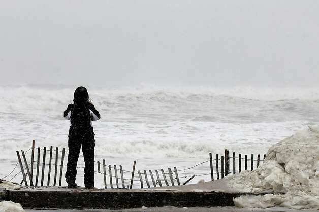 Judy Walton looks out over the foaming ocean in Salisbury, Mass. on Saturday, Feb. 9, 2013. A behemoth storm packing hurricane-force wind gusts and blizzard conditions swept through the Northeast overnight. Photo: Winslow Townson, Associated Press