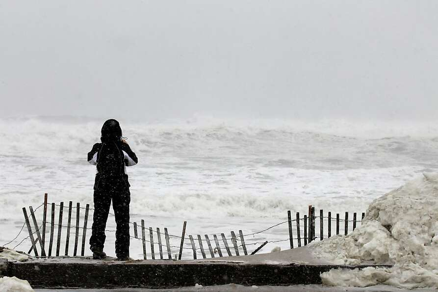 Judy Walton looks out over the foaming ocean in Salisbury, Mass. on Saturday, Feb. 9, 2013. A behemo