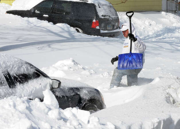 Tito Santana trudges his way across the street to help a neighbor shovel out after a blizzard pounded the region in West Haven, Conn. on Saturday February 9, 2013. Photo: Christian Abraham / Connecticut Post