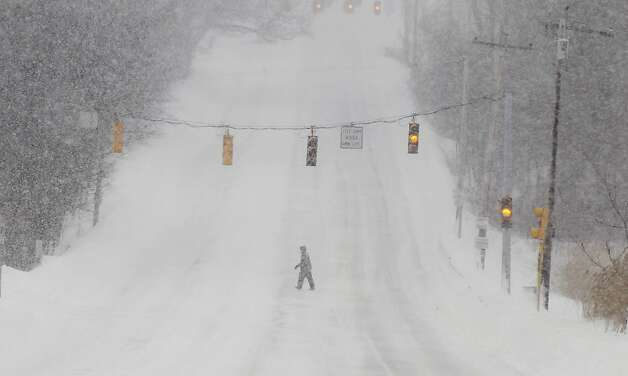 A pedestrian crosses a deserted street in North Andover, Mass. Saturday, Feb. 9, 2013 after a snowstorm came through dumping more than 2 feet of snow on New England. Photo: Winslow Townson, Associated Press