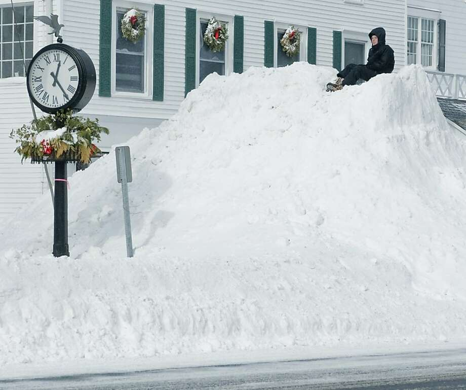 Gabe Altopp, 15 of Ridgefield, sits on top of a plowed pile of snow on Main Street in Ridgefield after the snowstorm had passed. Saturday, Feb. 9, 2013 Photo: Scott Mullin