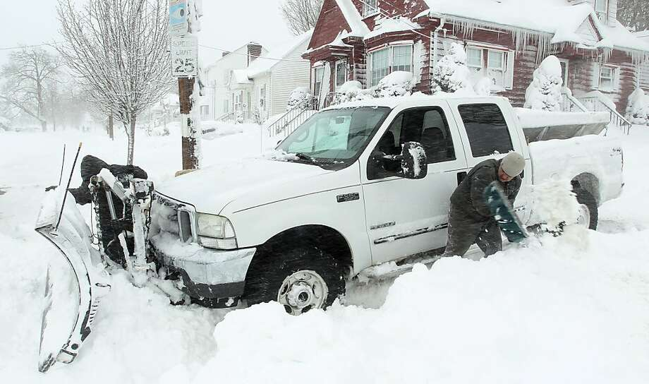 Michael Gelardi, right, and Larry Rose, left, attempt to dig out their snow plow after it got stuck in deep snow Saturday, Feb. 9, 2013, in Providence, R.I.  A howling storm across the Northeast left the New York-to-Boston corridor shrouded in 1 to 3 feet of snow Saturday, stranding motorists on highways overnight and piling up drifts so high that some homeowners couldn't get their doors open. More than 650,000 homes and businesses were left without electricity. Photo: Stew Milne, Associated Press