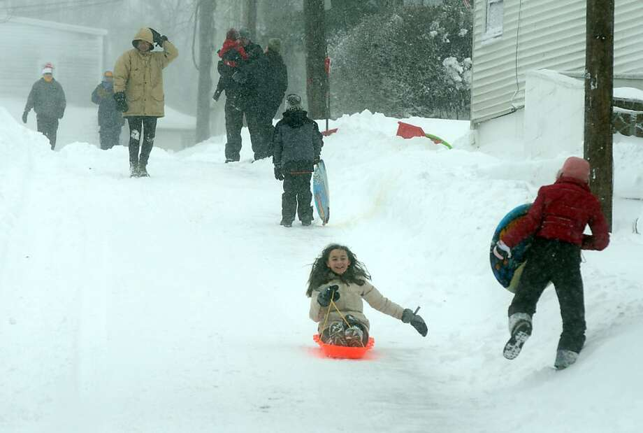 Kids and adults sled down Jefferson Street February 9, 2013 in Winthrop, Massachusetts. An overnight blizzard left one to two feet of snow in some areas, and coastal flooding is expected as the storm lingers into the day. Photo: Darren McCollester, Getty Images