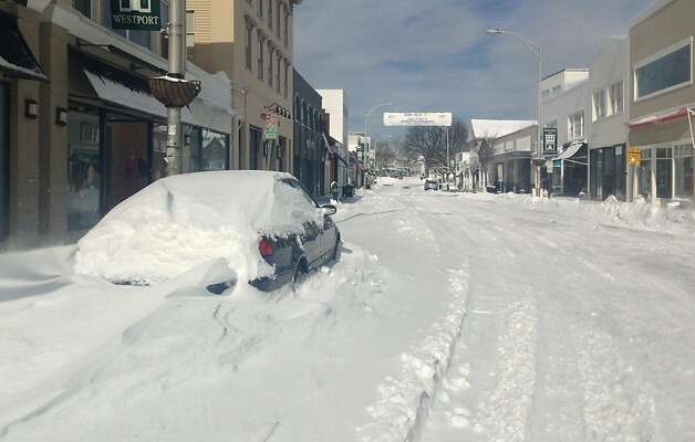 A car was marooned in a Main Street snow bank Saturday, but not much other activity was in evidence after a blizzard dumped 2 to 3 feet of snow on the town. Photo: Paul Schott