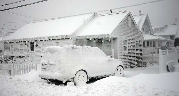 Wet snow coats houses and a vehicle in the Humarock coastal neighborhood of Scituate, Mass., Sat Feb. 9, 2013, after a heavy snowfall and high winds from a storm dumped more than 2 feet of snow on New England. Photo: Greg Derr, Associated Press