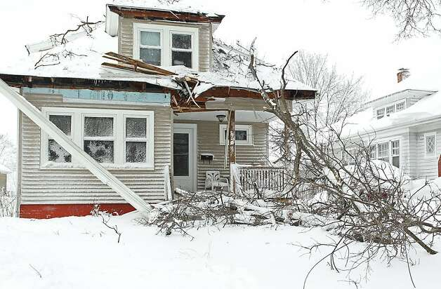A large limb from tree damaged the front of a house on River Street in Providence, R.I., after strong winds brought it down Saturday, Feb. 9, 2013. A behemoth storm packing hurricane-force wind gusts and blizzard conditions swept through the Northeast on Saturday, dumping more than 2 feet of snow on New England and knocking out power to 650,000 homes and businesses. Photo: Stew Milne, Associated Press