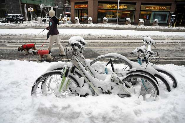 "People walk by a frozen bikes after winter storm Nemo covered New York City with 4 to 8 inches (10-20cms) of snow on February 9, 2013. The storm was forecast to bring the heaviest snow to the densely-populated northeast corridor so far this winter, threatening power and transport links for tens of millions of people and the major cities of Boston and New York. New York and other regional airports saw more than 4,500 cancellations ahead of what the National Weather Service called ""a major winter storm with blizzard conditions"" along most of the region's coastline. Photo: Mehdi Taamallah, AFP/Getty Images"