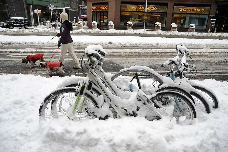 People walk by a frozen bikes after winter storm Nemo covered New York City with 4 to 8 inches (10-2