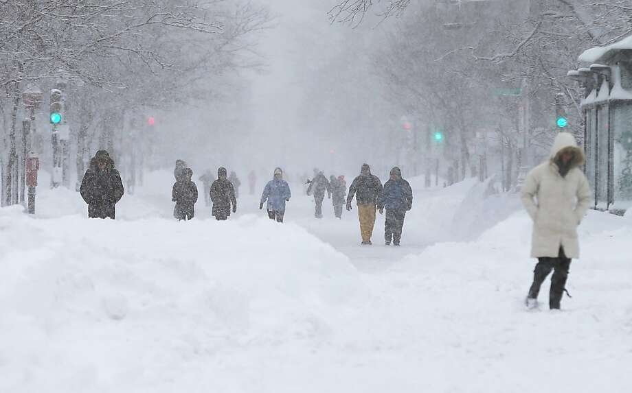 People walk in the snow during a lingering blizzard on February 9, 2013 in Boston, Massachusetts. The powerful storm has knocked out power to 650,000 and dumped more than two feet of snow in parts of New England. Photo: Mario Tama, Getty Images