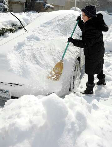Marina Sorokin sweeps snow off her daughter's car in Stamford, Conn., on Saturday, February 9, 2013. Photo: Lindsay Perry / Stamford Advocate