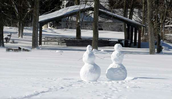 Snowmen sit constructed in Stamford, Conn., on Saturday, February 9, 2013. Photo: Lindsay Perry / Stamford Advocate