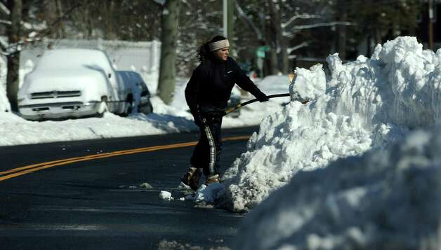 A woman clears off her car in Stamford, Conn., on Saturday, February 9, 2013. Photo: Lindsay Perry / Stamford Advocate